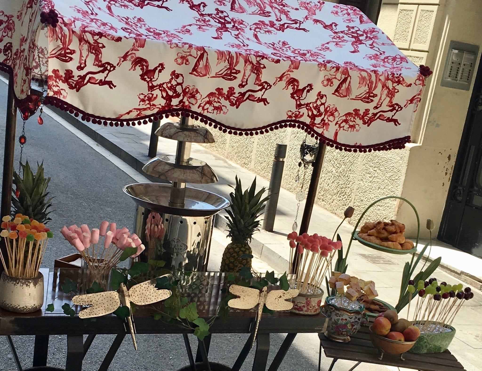 Carrito con fuente de chocolate y un toldo blanco con estampados rosas. Diferentes chuches y bollos para acompañar el chocolate caliente.